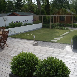 Decked patio leading to gravel then lawn with stepping stones